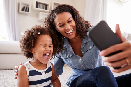 Young mother and toddler daughter taking selfie at home Stock Photo