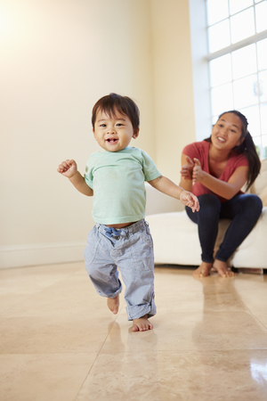 Eenjarige jongen die de eerste stapjes zet met moeder