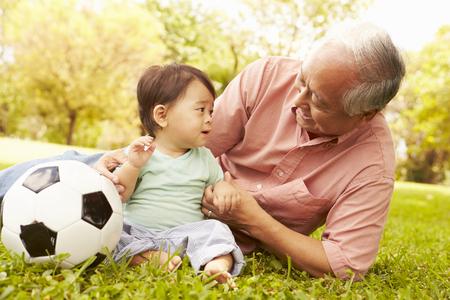 Großvater und Enkel spielen mit Fußball im Park