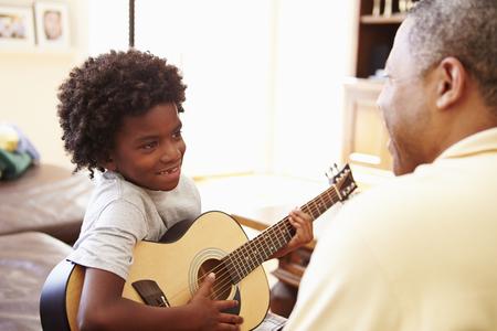 Grandfather Teaching Grandson To Play Guitar