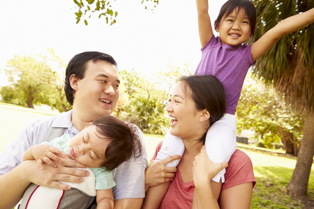 Family With Baby In Carrier Walking Through Park Stock Photo