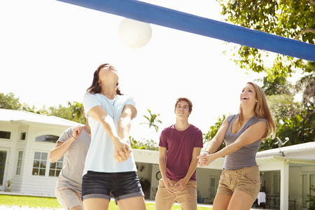 Group Of Young Friends Playing Volleyball Match