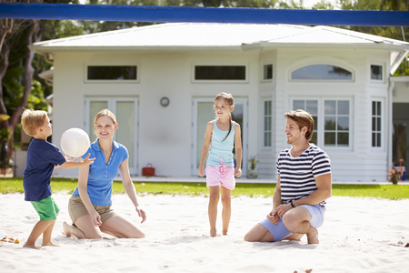 Family Playing Game Of Volleyball In Garden