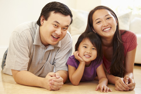 Portrait Of Family Lying On Floor At Home Stock Photo