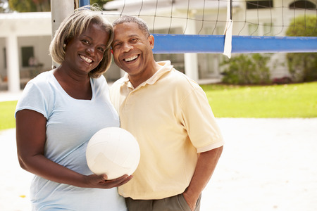 Senior Couple Playing Volleyball Together Stock Photo