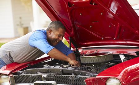 Retired Senior Man Working On Restored Car