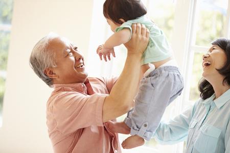 Grands-parents et petit-fils jouant ensemble à l'intérieur