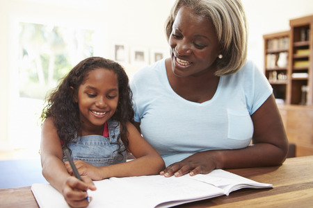 Grandmother Helping Granddaughter With Homework Stock Photo