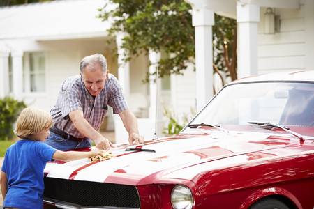 Grandfather And Grandson Cleaning Restored Classic Car