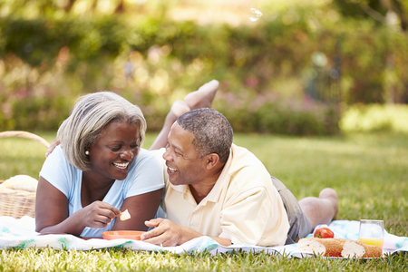 Senior Couple Having Picnic In Garden
