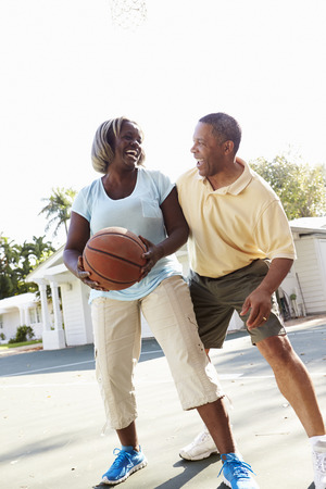 Senior Couple Playing Basketball Together Stock Photo