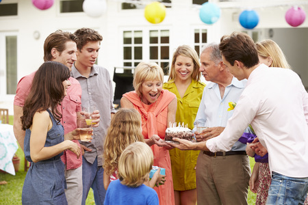 Mehrgenerationenfamilie, die Geburtstag im Garten feiert Standard-Bild