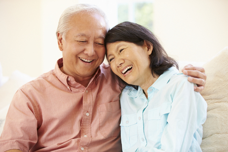 Senior Asian Couple Sitting On Sofa At Home Together 스톡 콘텐츠