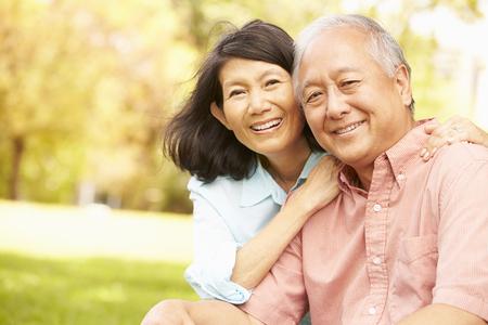 Retrato de pareja asiática senior sentados juntos en el parque