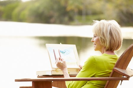 Senior Woman Sitting At Outdoor Table Painting Landscape