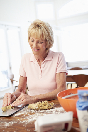Senior Woman Baking Cookies In Kitchen