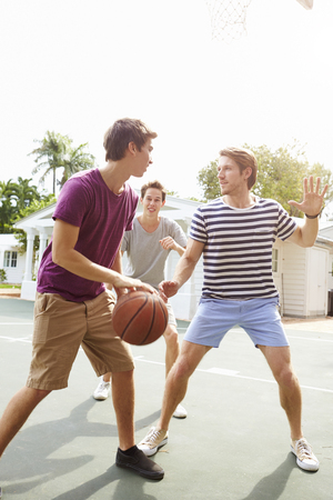 Group Of Young Men Playing Basketball Match