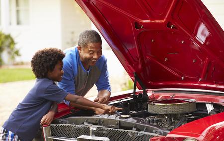 Abuelo y nieto trabajando en un coche clásico restaurado