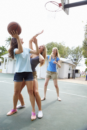 Group Of Young Women Playing Basketball Match