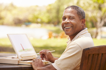 Senior Man Sitting At Outdoor Table Painting Landscape Stock Photo