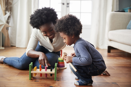 Mother And Young Son Playing With Wooden Toy At Home 版權商用圖片 - 101931677
