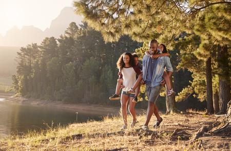 Ouders geven kinderen meeliften op de wandeling langs het meer Stockfoto