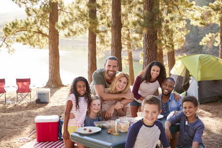 Portrait Of Family With Friends Camping By Lake In Forest Stok Fotoğraf