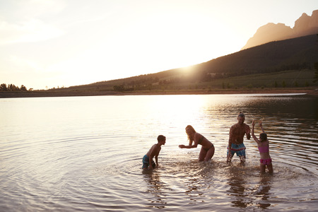 Family Enjoying Evening Swim In Countryside Lake Banque d'images - 102853801