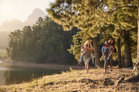 Group Of Young Friends Enjoying Walk By Lake On Hiking Adventure Stock Photo