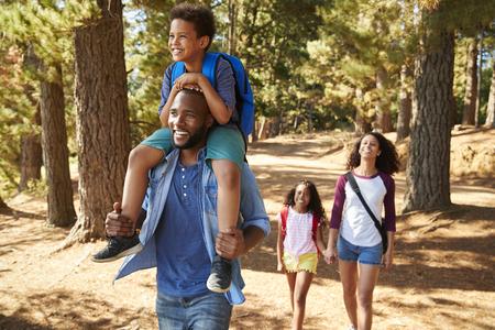 Familie op wandelavontuur door bos Stockfoto