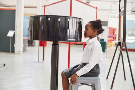 Schoolgirl sitting in front of zoetrope at a science centre