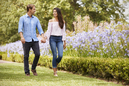 Couple Holding Hands On Romantic Walk In Park Together Stock Photo