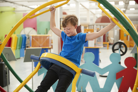 Young white boy in science centre using a human gyroscope Stock Photo - 102854228