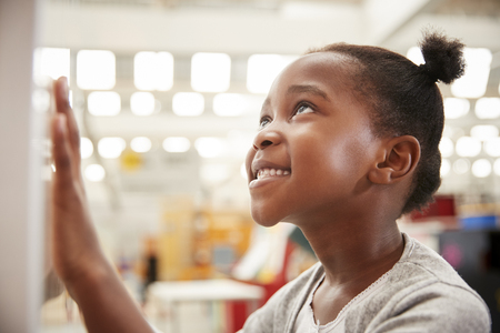 Young black girl looking at a science exhibit, close up Stock Photo
