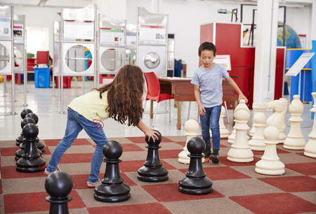 Schoolchildren playing giant chess at a science centre Stock Photo