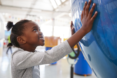 Young black girl holding a giant globe at a science centre Stock Photo