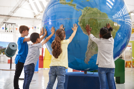 Group of school kids holding giant globe at a science centre