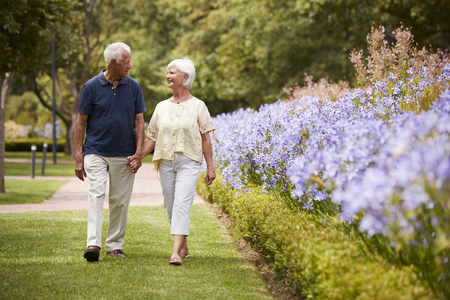 Senior Couple Holding Hands On Romantic Walk In Park Together