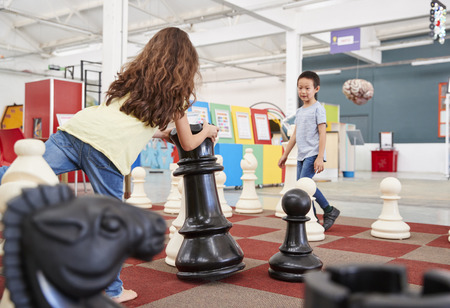 Two children playing giant chess at a science centre