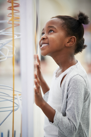 Young black girl looking at a science exhibit, vertical