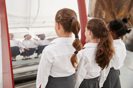 Schoolgirls looking in a curved mirror at a science centre