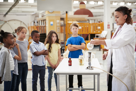 Kids watching lab technician carry out a science  experiment Stock Photo
