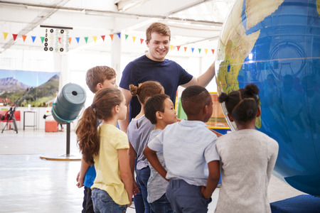 School kids looking at a giant globe at a science centre Stock Photo