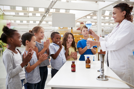 Lab technician showing excited kids a science experiment Stock Photo