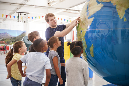 Kids watch presentation with giant globe at a science centre