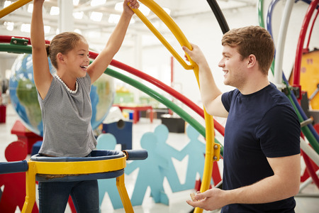 Teacher talking to young white girl in a human gyroscope Stock Photo
