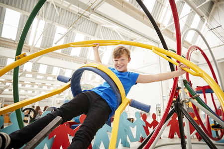 Young white boy having fun using a human gyroscope Stock Photo