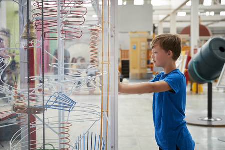 Young boy stands looking at a science exhibit, side view Stock Photo