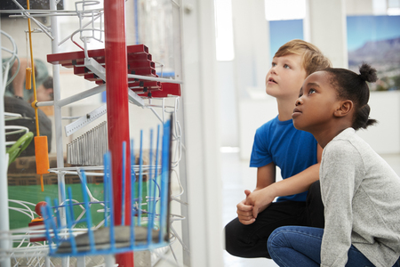 Two kids kneeling and looking at a science exhibit