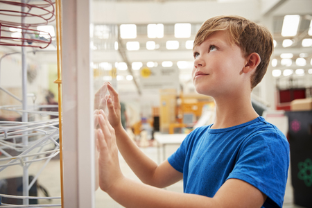 Young white boy looking up at science exhibit, close up Stock Photo